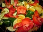 Порезанные ломтиками помидоры и огурцы добавьте на сковородку, в которой жарятся морковь, лук и перец.