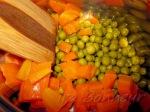Морковь нарежьте кубиками, сложите в кастрюлю и добавьте горошек